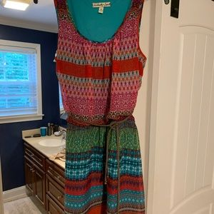 Bright colored pattern dress with tan belt.